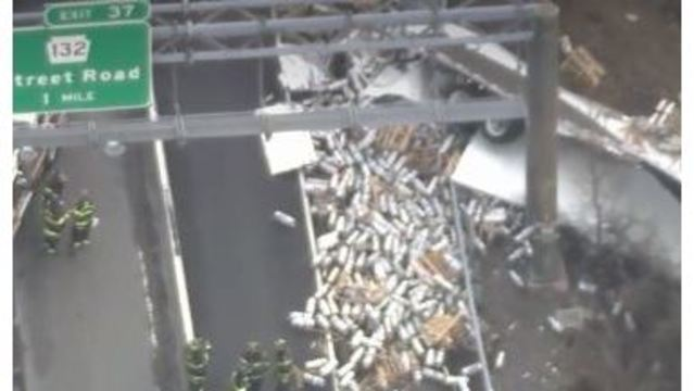 Truck falls off overpass, dumps beer kegs onto road